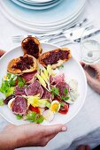 Riviera salad with raw tuna fish fillets and crostini with tapenade
