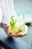 A woman holding a glass of caipirovka with mint