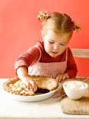 Little girl pinching a nibble of pie