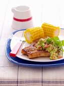 Pork steak with guacamole and corn on the cob (Mexico)