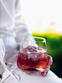 A person holding a glass of verjus (unripened grape juice) with soda