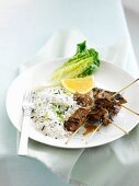 Pork kebabs with rice and spring onions