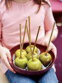 A girl holding a bowl of toffee apples