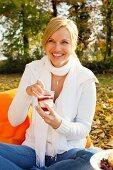 Woman eating yoghurt dessert at autumn picnic
