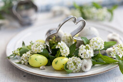 A rabbit-shaped biscuit cutter on a plate with catkins, sugar eggs and spiraea