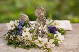 A wreath of forget-me-not, garden jasmine and sloe flowers around a silver cockerel