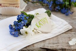 A name written on a heart with a bunch of forget-me-not and garden jasmine