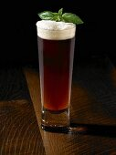 Tall Glass of Amber Beer with a Basil Garnish