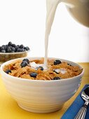 Milk Pouring into a Bowl of Wheat Flake Cereal with Blueberries