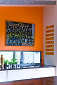 A corner of a kitchen with a bright orange wall and a large picture of letters