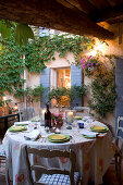 Dinner in a courtyard - candle lanterns on set table in front of climber-covered house facade