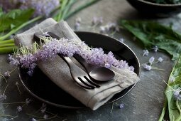 A place setting decorated with an allium flower ribbon