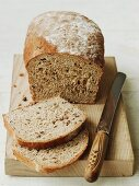 Organic country bread on a chopping board (sliced)