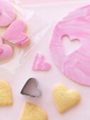Pink heart-shaped biscuits being cut out