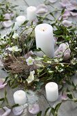 A wreath of pink roses, mistletoe and hellebores with a candle