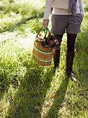Frau hält Korbtasche mit Blumen