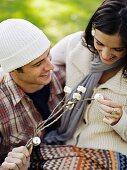 Junges Paar mit gegrillen Marshmallow-Spiesschen