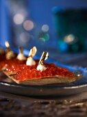 Salmon caviar tartlets topped with gold leaf