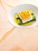 Cod fillet with orange zest on zucchini slices