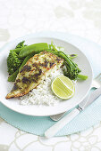 Fish with a green chilli crust on rice and green vegetables