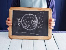 A cartoon fish drawn on a chalkboard