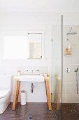 Freistehender Waschtisch mit Wandarmatur und Spiegel neben Duschtrennwand