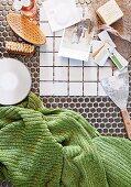 weiße Musterfliesen und Spachtel neben Waschutensilien und grünem Handtuch auf Mosaikfliesenboden