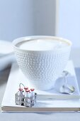 A cappuccino with a mini milk bottle basket