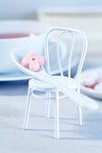 A sugar flower on a coffee spoon on a doll's house chair
