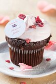 Chocolate cupcake topped with cream, candied rose petals and a Union Jack decoration