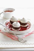 Mini meringue sandwiches filled with chocolate in raspberry sauce
