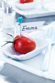 A place card made using a tomato, a need and sticky tape