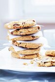 A stack of chocolate and nut cookies between sheets of baking paper