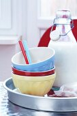 Muesli bowls, spoons and a bottle of milk on a tray