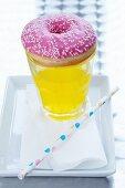 A doughnut on top of a glass of fizzy pop