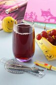 A glass of red grape juice with school things