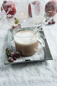 Cup of hot chocolate on metal tray in artificial snow