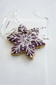 A snowflake biscuits decorated with purple icing sugar