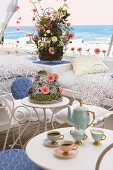Coffee table with elegant coffee service; a flower arrangement with pink Gerberas behind it