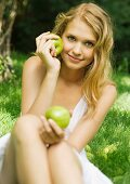 Young woman sitting in grass, holding up apples
