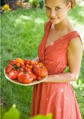 Woman holding bowl full of tomatoes