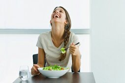 Teen girl eating salad, laughing with head back