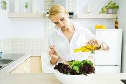 Woman standing in kitchen, pouring olive oil over salad
