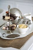 Biscuits and packaged chocolate bars on a tiered cake stand next to assorted sugar bowls on a vintage porcelain platter