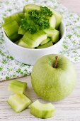 Sliced cucumber and a green apple