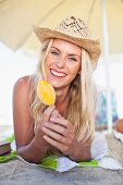 Smiling woman eating popsicle on beach