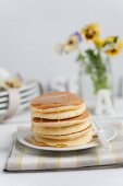 A stack of pancakes filled with vanilla cream and maple syrup