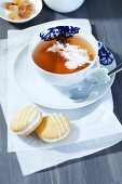 A cup of tea with black tea and cream, rock sugar and biscuits