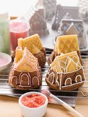 Small house-shaped cakes with the baking tins in the background