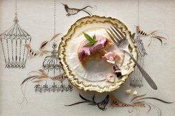 A raspberry mousse tartlet with marijuana, half eaten